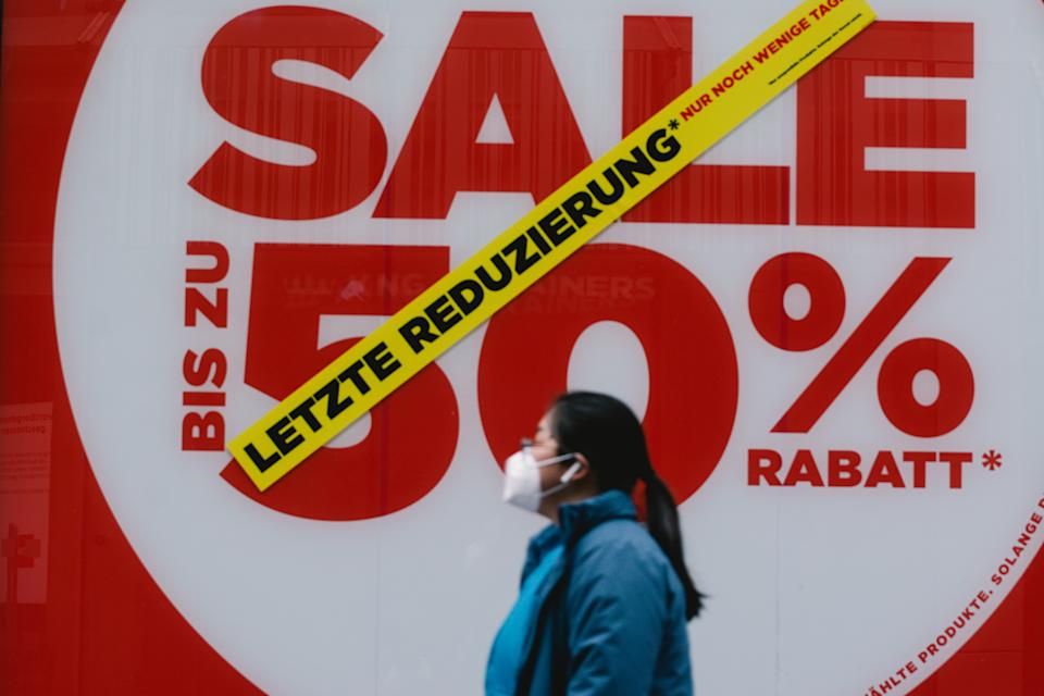 a woman walks pass a big 50 percent sale sign in a retailer store  amid the Coronavirus lockdown in Cologne (Photo by Ying Tang/NurPhoto via Getty Images)