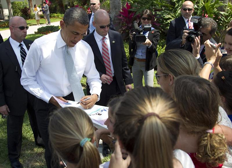 President Barack Obama greets residents waiting for him as he arrives for a campaign event, Tuesday, April 10, 2012, in Palm Beach Gardens, Fla. (AP Photo/Carolyn Kaster)