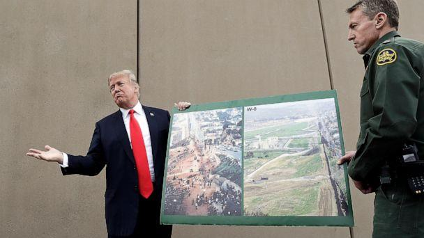 PHOTO: In this March 13, 2018, file photo, President Donald Trump holds a poster with photographs of the U.S.-Mexico border area as he reviews border wall prototypes in San Diego with Rodney Scott, the U.S. Border Patrol's San Diego sector chief. (Evan Vucci/AP)