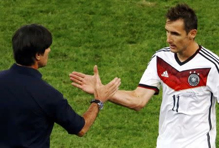 Germany's Miroslav Klose (R) shakes hands with coach Joachim Loew as he leaves the pitch during their 2014 World Cup final against Argentina at the Maracana stadium in Rio de Janeiro July 13, 2014. REUTERS/Leonhard Foeger
