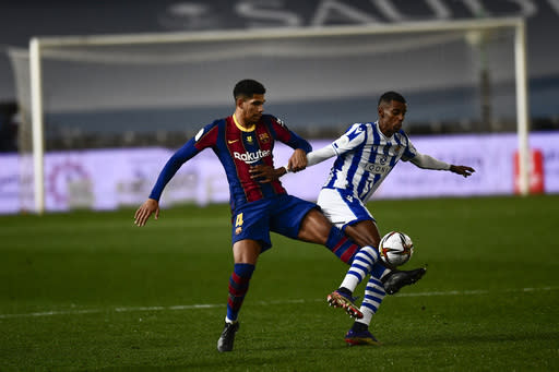 Barcelona's Ronald Araujo, left, vies for the ball with Real Sociedad's Alexander Isak during Spanish Super Cup semi final soccer match between Barcelona and Real Sociedad at Nuevo Arcangel stadium in Cordoba, Spain, Wednesday, Jan. 13, 2021. (AP Photo/Jose Breton)