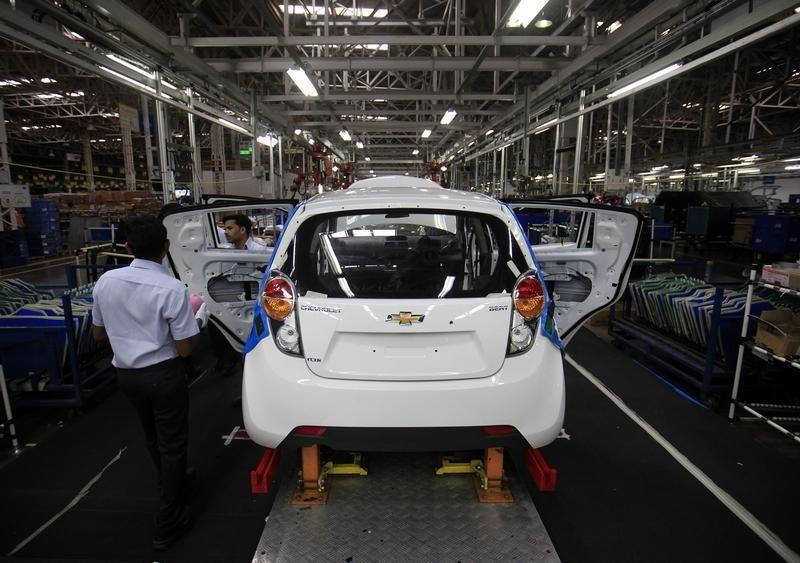 eEmployees work on a Chevrolet Beat car on an assembly line at the General Motors plant in Talegaon