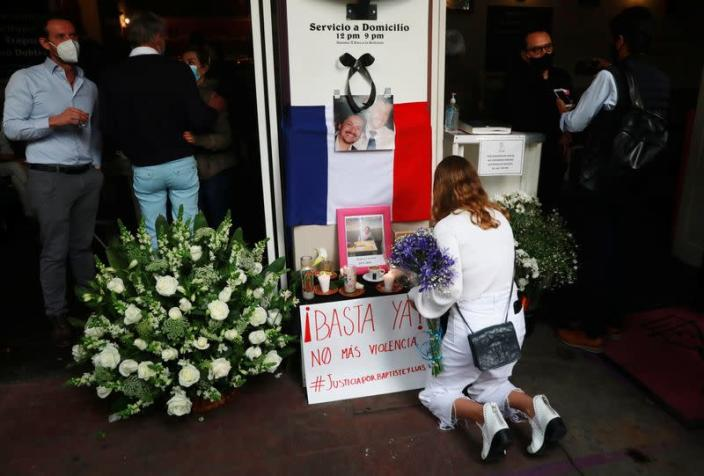 A member of the French community living in Mexico places flowers at an altar outside a restaurant owned by French businessman Baptiste Jacques Daniel Lormand after he was found murdered, in Mexico City