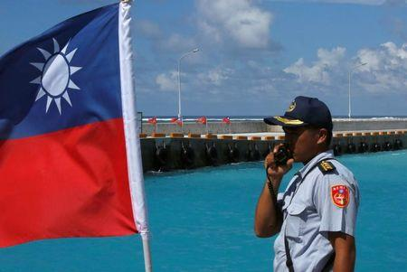 FILE PHOTO: A member of the Taiwanese Coast Guard stands guard next to a Taiwanese flag on Itu Aba, which the Taiwanese call Taiping, at the South China Sea