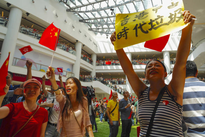 Pro-China protesters wave China national flags at a shopping mall in Hong Kong, Friday, Sept. 13, 2019. Protest-related activities are expected to continue Friday, when Chinese celebrate the Mid-Autumn Festival with lanterns and mooncakes. (AP Photo/Vincent Yu)