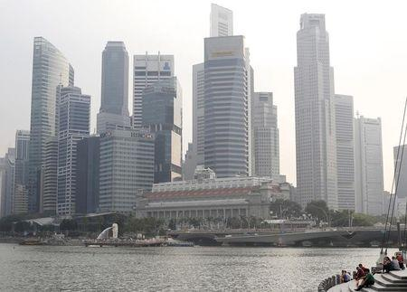 People sit along the Marina Bay area in the hazy skyline of Singapore