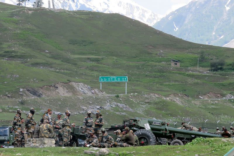 Indian army soldiers rest next to artillery guns at a makeshift transit camp before heading to Ladakh, near Baltal