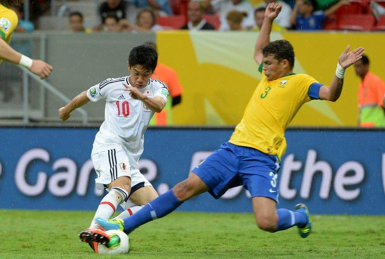 Japan's Shinji Kagawa (L) is denied by Brazil defender Thiago Silva on June 15, 2013