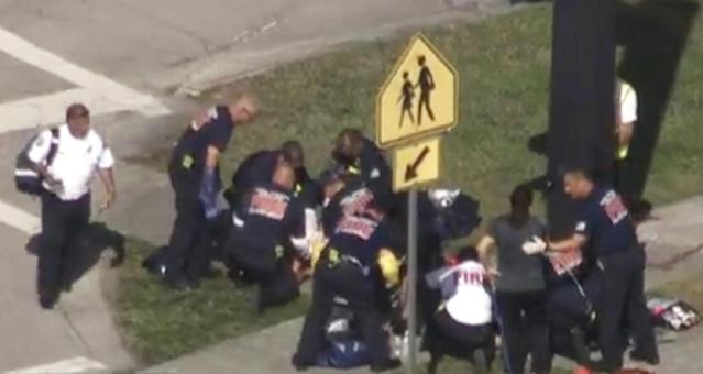 <p>Rescue workers deal with a victim near Marjory Stoneman Douglas High School during a shooting incident in Parkland, Florida, U.S. February 14, 2018 in a still image from video. (Photo: WSVN.com via Reuters) </p>