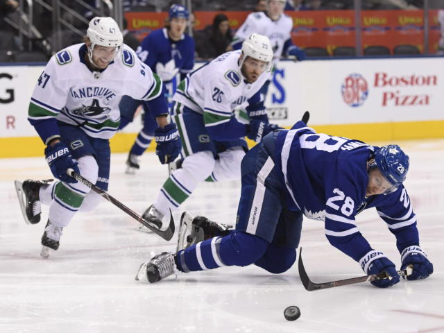 Toronto Maple Leafs right wing Connor Brown (28) falls to the ice as Vancouver Canucks left wing Sven Baertschi (47) and left wing Antoine Roussel (26) move towards the puck during the second period of an NHL hockey game, Saturday, Jan. 5, 2019, in Toronto. (Nathan Denette/The Canadian Press via AP)