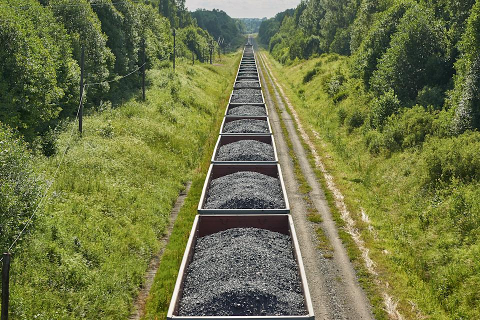 Set of train cars with coal transport by rail - countryside view
