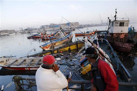 Fishermen look at sunken boats, after a series of aftershocks, in the northern port of Iquique April 3, 2014. REUTERS/Ivan Alvarado