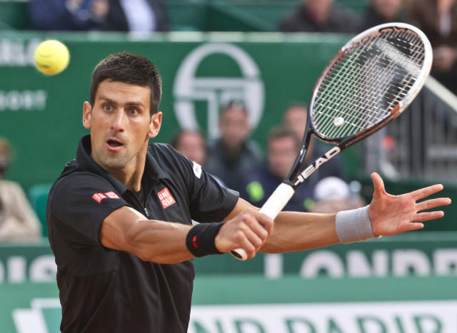 Novak Djokovic of Serbia returns the ball to Guillermo Garcia-Lopez of Spain during their quarterfinals match of the Monte Carlo Tennis Masters tournament in Monaco, Friday, April 18, 2014. (AP Photo/Michel Euler)