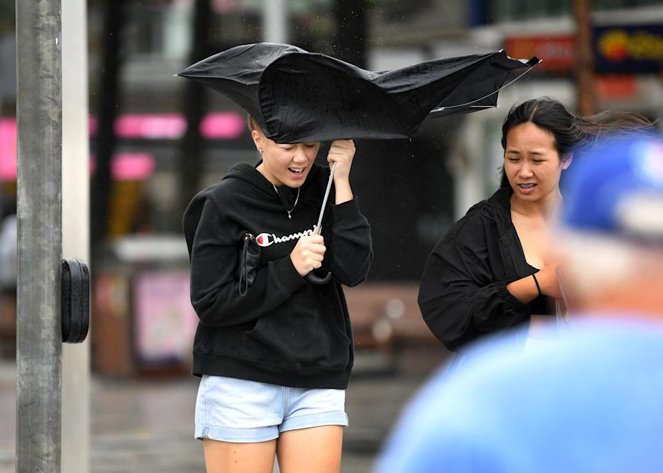 A teenage girl struggles with her umbrella in stormy conditions at Surfers Paradise on the Gold Coast.