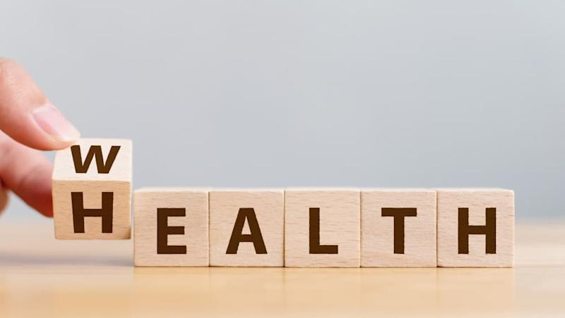 Hand flip wooden cube with word wealth to health.