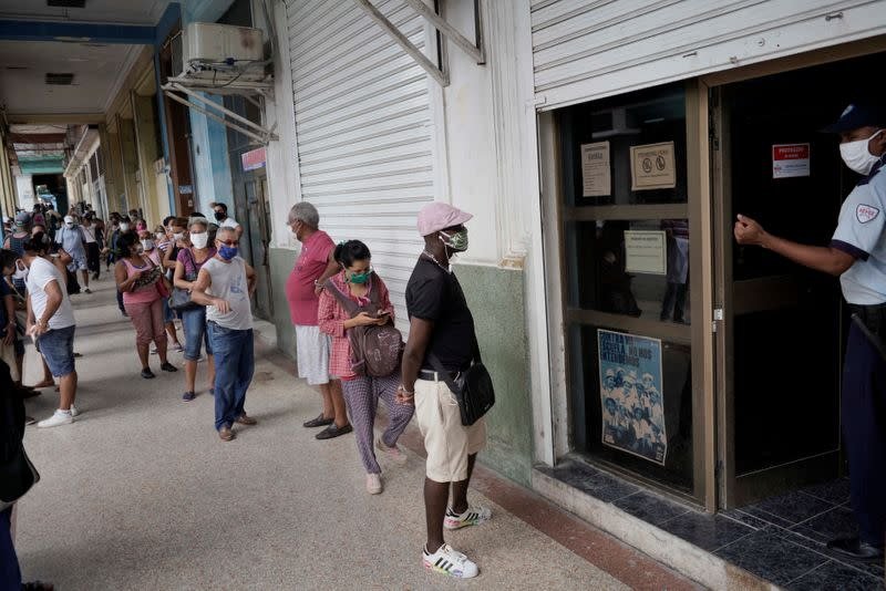 People wait in line to enter a currency exchange office in Havana, Cuba