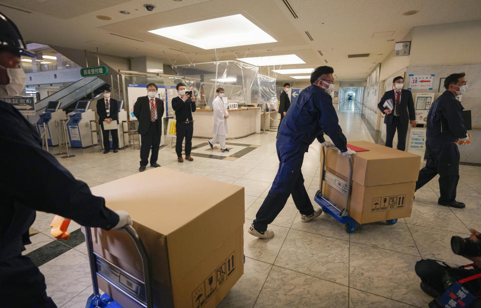 Delivery staff bring Pfizer Inc's COVID-19 vaccine to a Tokyo hospital, Japan, Tuesday, Feb. 16, 2021. Japan's COVID-19 vaccinations are scheduled to begin Wednesday after the government granted belated first approval to a shot co-developed by Pfizer Inc. (Kimimasa Mayama/Pool Photo via AP)