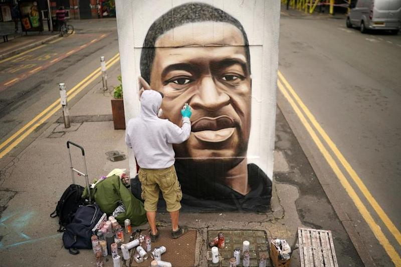 Graffiti artist Akse spray paints the mural of George Floyd in Manchester's northern quarter on June 3: Getty Images