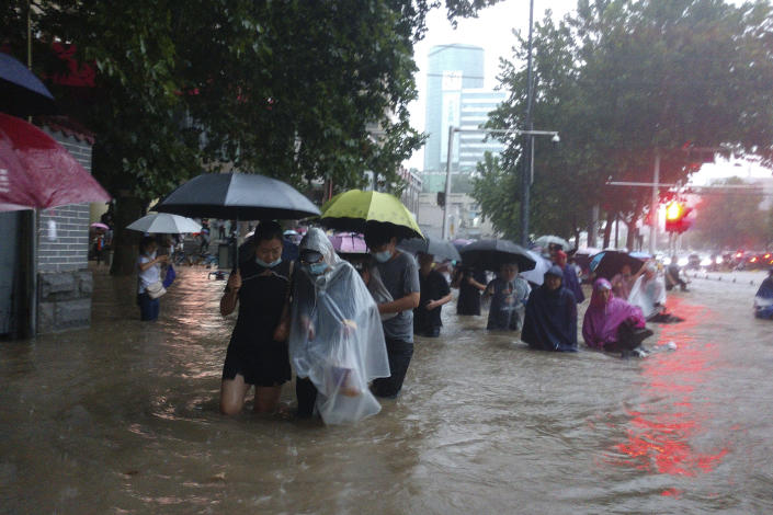 People move through flood water after a heavy downpour in Zhengzhou city, central China's Henan province on Tuesday, July 20, 2021. Heavy flooding has hit central China following unusually heavy rains, with the subway system in the city of Zhengzhou inundated with rushing water and thousands of residents having to be relocated. (Chinatopix Via AP)