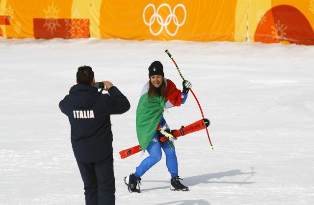 Alpine Skiing - Pyeongchang 2018 Winter Olympics - Women's Downhill - Jeongseon Alpine Centre - Pyeongchang, South Korea - February 21, 2018 - Gold medallist Sofia Goggia of Italy poses for a team member during the flower ceremony. REUTERS/Leonhard Foeger