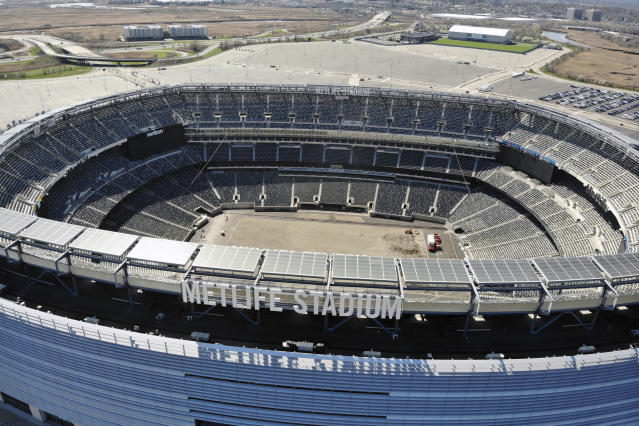 FILE - In this April 6, 2020, file photo, an empty MetLife Stadium in East Rutherford, N.J. , is viewed. Timing favored the NFL over other major pro sports leagues in trying to figure out how to keep the coronavirus pandemic from wrecking the 2020 season. America's most popular sport has another big advantage if the games are played: TV money. While NFL owners could lose billions collectively with limited capacities in stadiums or no fans at all, the league is well-positioned financially because of lucrative media contracts approaching $10 billion in a full 2020 season. (AP Photo/Ted Shaffrey, File)