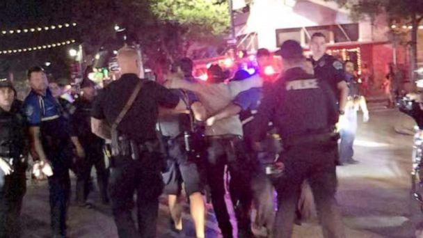 PHOTO: Police officers escort a victim (C) after gunfire erupted at a busy entertainment district in Austin, Texas, June 12, 2021, in this still image taken from video provided on social media. (Jessica Moss via Reuters)