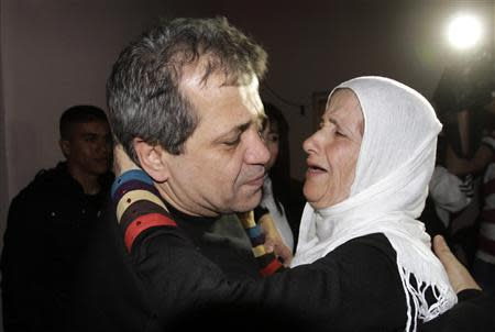 Released Palestinian prisoner Moayyad Hajji, 46, who was arrested in 1992, hugs his sister upon his arrival at his family's house in the West Bank village of Burqa near Nablus