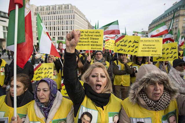 <p>Protesters hold signs and flags of the Iranian consitutional monarchy era as they protest near Brandenburg Gate in Berlin, Germany, Jan. 6, 2018. (Photo: OMER MESSINGER/EPA-EFE/REX/Shutterstock) </p>