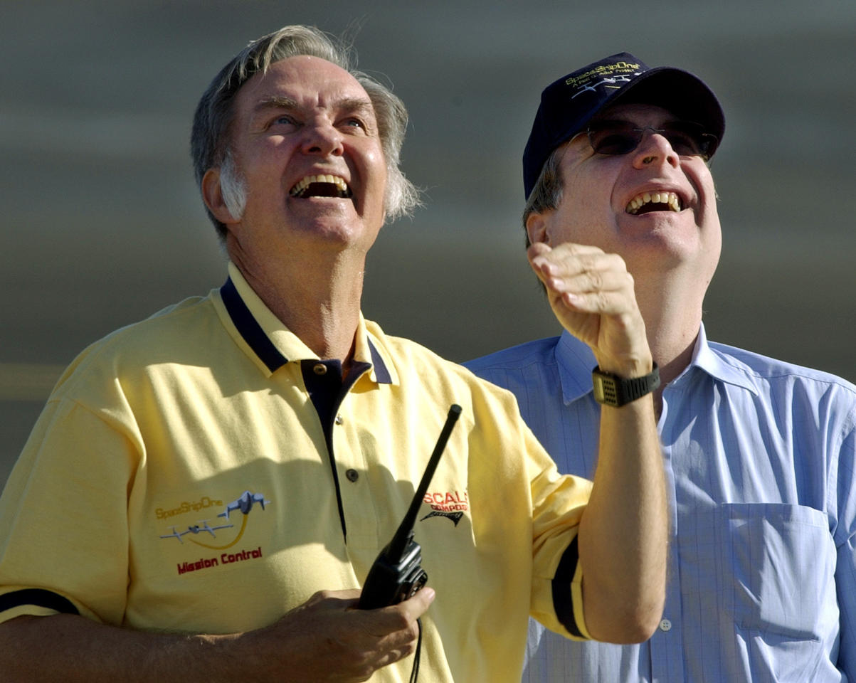 FILE- In this June 21, 2004, file photo project designer Burt Rutan, left, and sponsor Paul Allen watch the approach and landing of SpaceShipOne after a trip to suborbital space at Mojave, Calif. Prior to his death on Monday, Oct. 15, 2018, Allen invested large sums in technology ventures, research projects and philanthropies, some of them eclectic and highly speculative. Outside of bland assurances from his investment company, no one seems quite sure what happens now. (AP Photo/Reed Saxon, File)