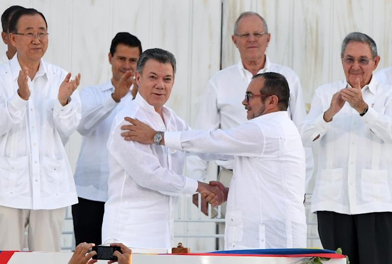 "Colombian President Juan Manuel Santos (L at centre) and the head of the FARC guerrilla Rodrigo ""Timochenko"" Londono shake hands during the signing of the historic peace agreement between the Colombian government FARC September 26, 2016"