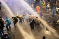 FILE - In this Oct. 16, 2020, file photo, pro-democracy demonstrators face water cannons as police try to disperse them from their protest venue in Bangkok, Thailand. Fed up with an archaic educational system and enraged by the military's efforts to keep control over their nation, a student-led campaign has shaken Thailand's ruling establishment with the most significant campaign for political change in years. (AP Photo/Gemunu Amarasinghe, File)