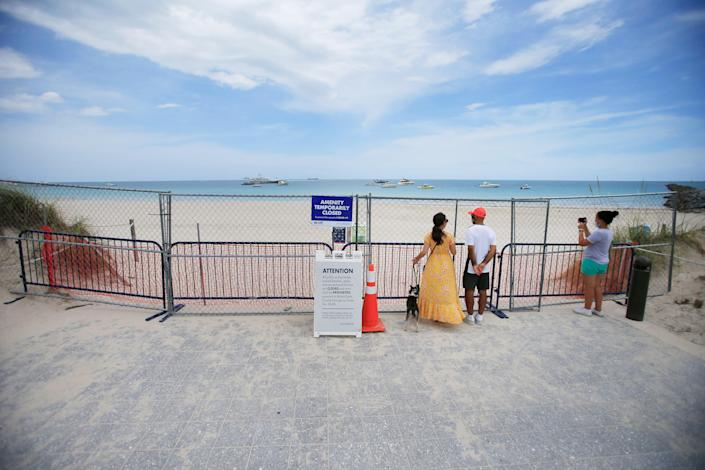 People look through fencing next to signage indicating that the beach is temporarily closed in South Pointe park on July 4, 2020, in the South Beach neighborhood of Miami Beach. / Credit: Cliff Hawkins / Getty