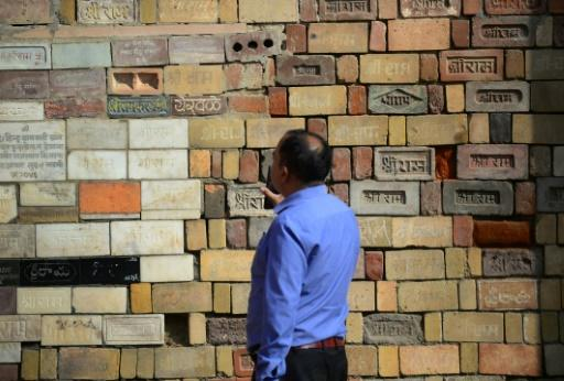 A Hindu devotee examines bricks for the proposed temple