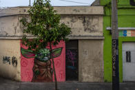 """A graffiti of """"The Child,"""" dubbed """"Baby Yoda"""" character, wearing a face mask, is painted on a wall in Guatemala City, Monday, April 6, 2020. (AP Photo/Moises Castillo)"""