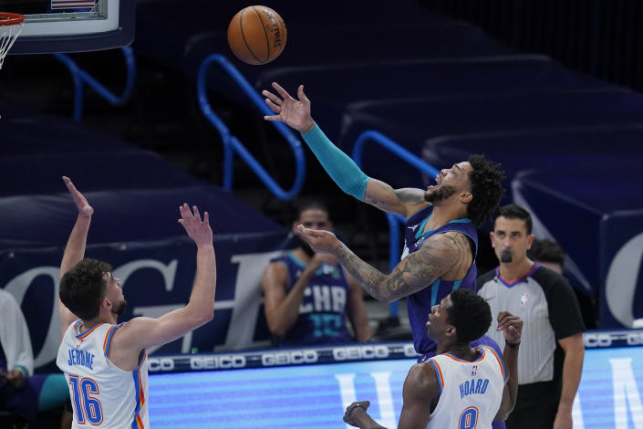 Charlotte Hornets forward Miles Bridges, rear, shoots in front of Oklahoma City Thunder guard Ty Jerome (16) and forward Jaylen Hoard (8) in the first half of an NBA basketball game Wednesday, April 7, 2021, in Oklahoma City. (AP Photo/Sue Ogrocki)