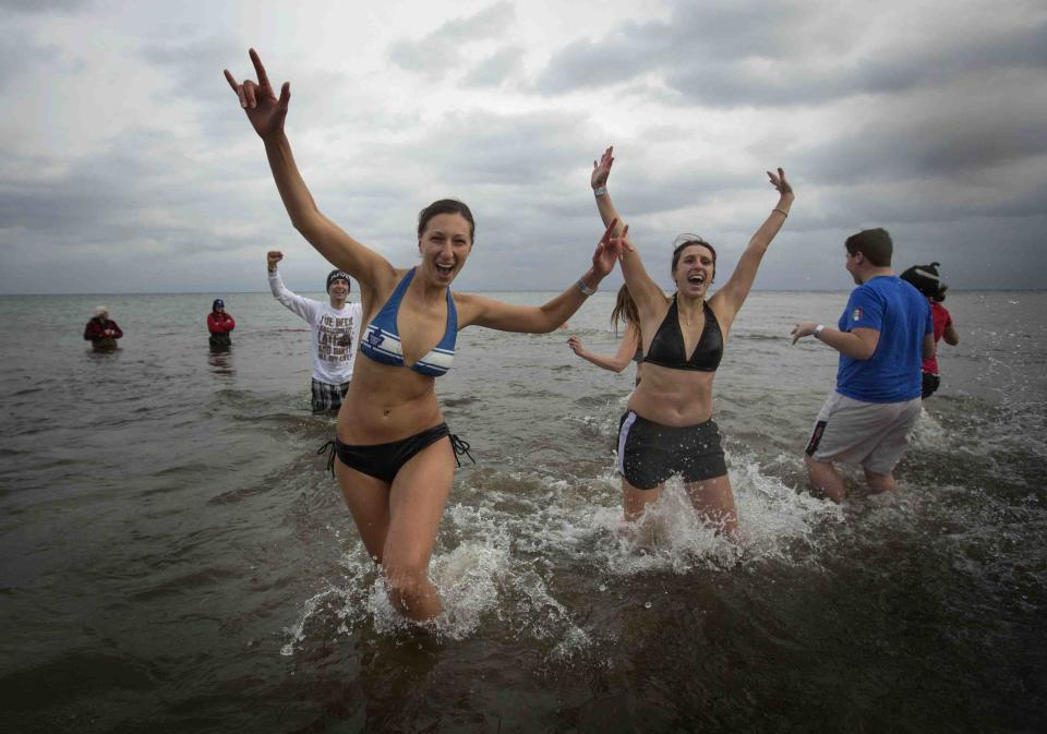 """Participants take part in Courage Polar Bear Dip at Coronation Park in Oakville January 1, 2015. This year's edition of the Courage Polar Bear Dip, in which hundreds of participants ran into Lake Ontario in subfreezing temperatures, will raise money for the """"Rwanda: Right to Clean Water"""" project. REUTERS/Mark Blinch (CANADA - Tags: SOCIETY ENVIRONMENT)"""