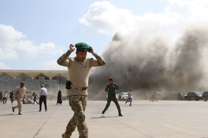 A security personnel member reacts as dust rises after explosions hit Aden airport, upon the arrival of the newly-formed Yemeni government in Aden