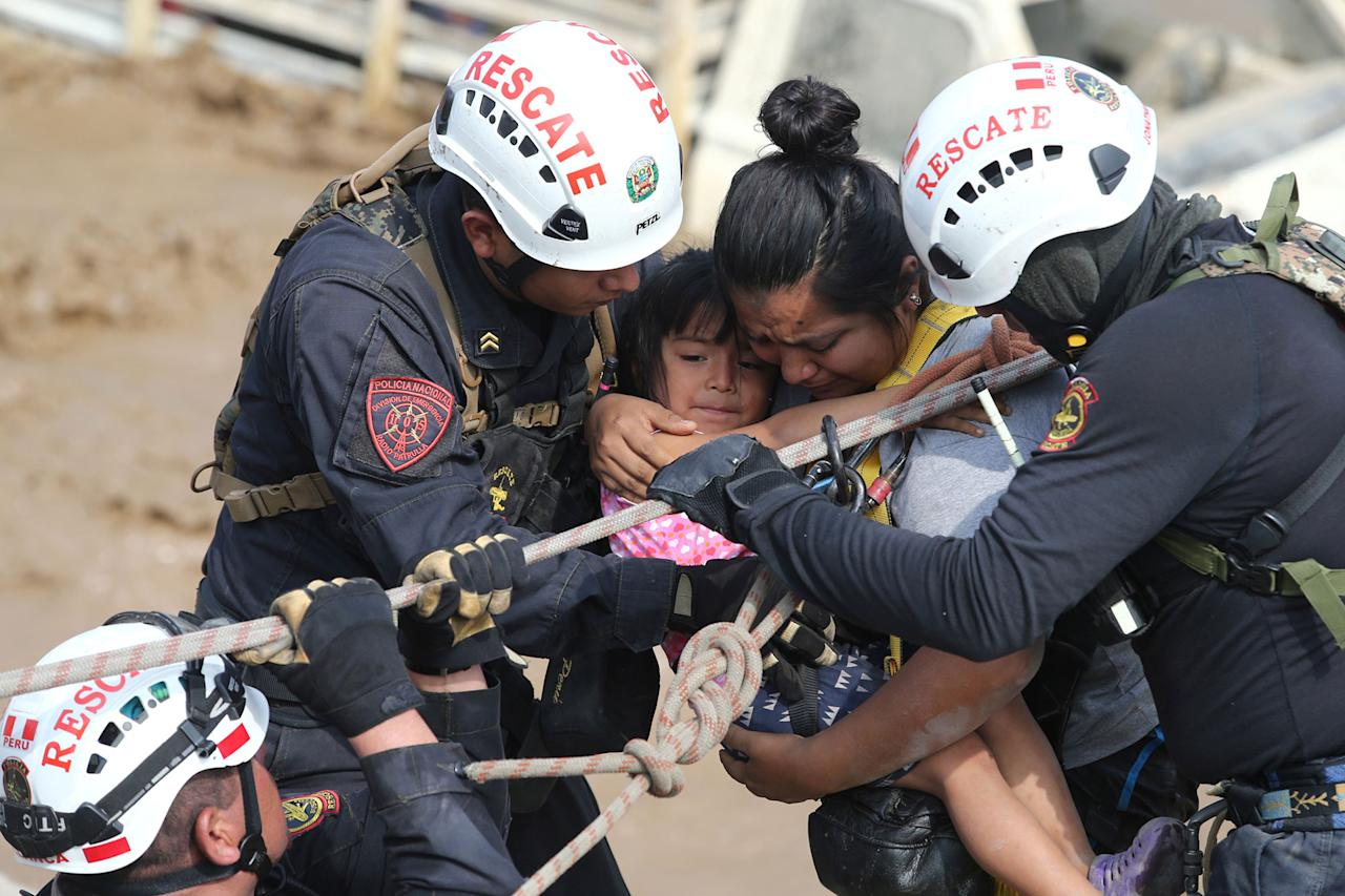 <p>A woman and a child get rescued after a massive landslide and flood in the Huachipa district of Lima, Peru, March 17, 2017. (Guadalupe Pardo/Reuters) </p>