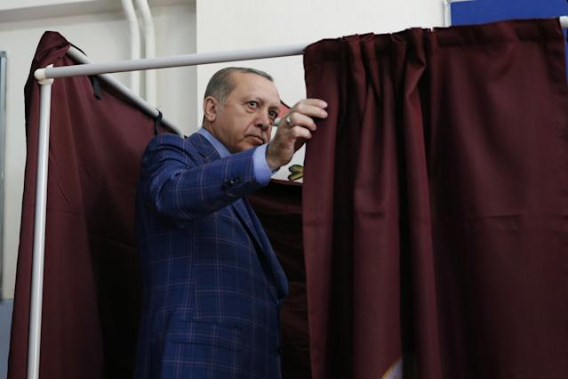 <p>Turkey's President Recep Tayyip Erdogan enters a voting booth inside a polling station in Istanbul, Turkey, on Sunday, April 16, 2017. (AP Photo/Lefteris Pitarakis) </p>