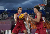 Belgium's Nick Celis (5) passes to teammate Thibaut Vervoort (2) as Latvia's Edgars Krumins watches during a men's 3-on-3 basketball game at the 2020 Summer Olympics, Saturday, July 24, 2021, in Tokyo, Japan. (AP Photo/Jeff Roberson)