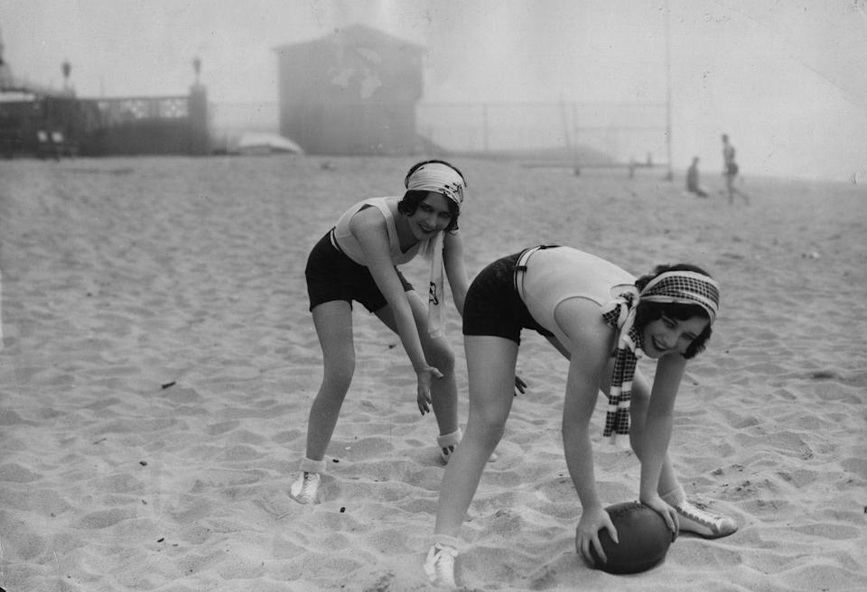 <p>Joan Crawford and Dorothy Sebastian play a friendly game of football while spending the day at the beach in 1927. </p>
