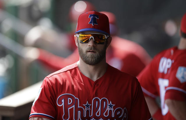 FILE - In this March 11, 2019 file photo Philadelphia Phillies right fielder Bryce Harper walks in the dugout before a spring training baseball game against the Tampa Bay Rays in Clearwater, Fla. Harper came to Philadelphia to do the one thing he didn't accomplish in Washington: Win in October. The Phillies gave him the biggest contract in baseball history to deliver. The 26-year-old slugger was a six-time All-Star, 2012 NL Rookie of the Year and 2015 NL Most Valuable Player during seven seasons with the Nationals. But he couldn't help Washington win a postseason series in four tries. (AP Photo/Chris O'Meara, file)