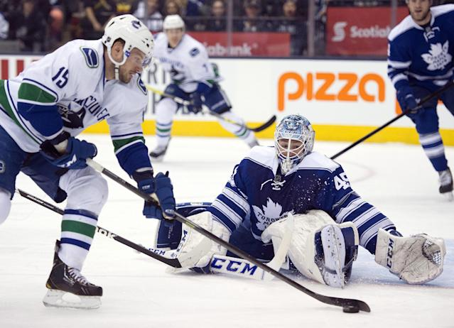 Toronto Maple Leafs goaltender Jonathan Bernier goes down to make a save on Vancouver Canucks right winger Brad Richardson (15) during the first period of an NHL hockey game, Saturday, Feb. 8, 2014 in Toronto. (AP Photo/The Canadian Press, Frank Gunn)