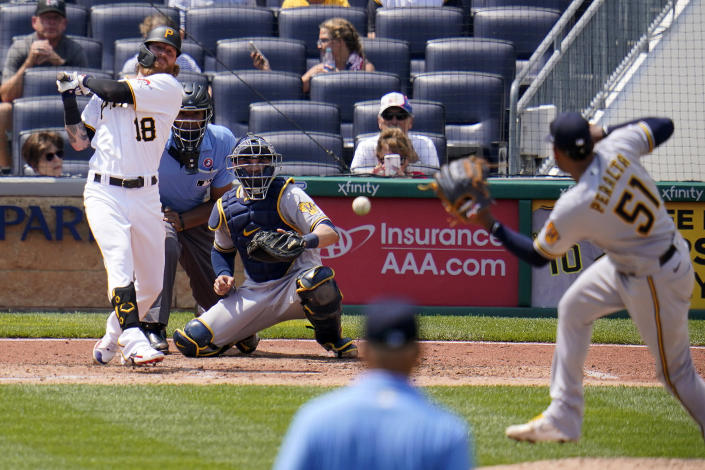 Pittsburgh Pirates' Ben Gamel (18) singles up the middle past Milwaukee Brewers relief pitcher Freddy Peralta (51) during the sixth inning of a baseball game in Pittsburgh, Sunday, July 4, 2021. (AP Photo/Gene J. Puskar)