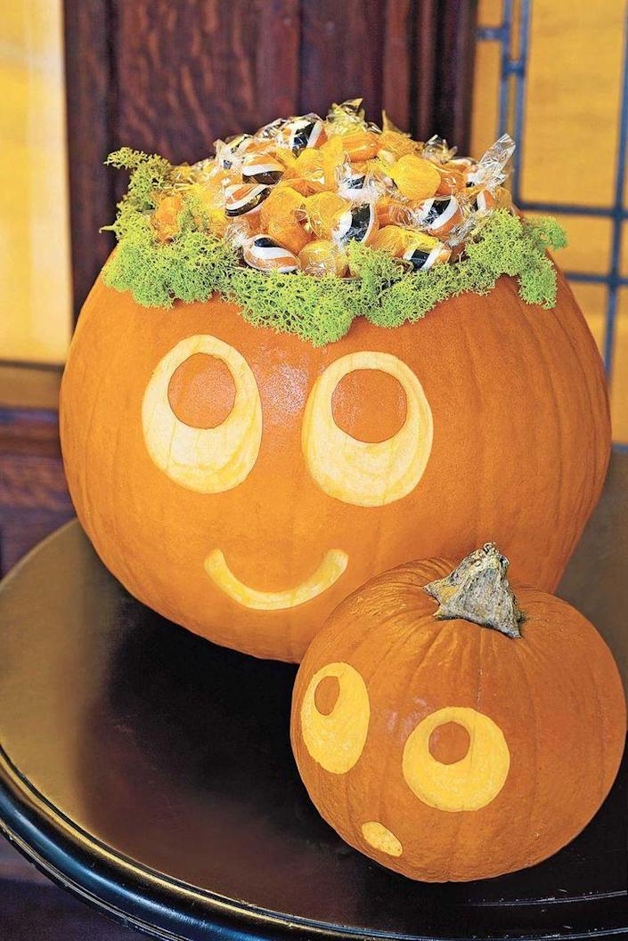 """<p>There's no better way to serve candy than in the head of a cute carved pumpkin. To make it, simply carve out a pumpkin, line it with faux moss, and fill it with colorful wrapped candies in shades of black and orange.</p><p><a class=""""link rapid-noclick-resp"""" href=""""https://www.amazon.com/Super-Moss-59834-21580-B00I6AJ7GY/dp/B00I6AJ7GY?tag=syn-yahoo-20&ascsubtag=%5Bartid%7C10070.g.2488%5Bsrc%7Cyahoo-us"""" rel=""""nofollow noopener"""" target=""""_blank"""" data-ylk=""""slk:SHOP FAUX MOSS"""">SHOP FAUX MOSS</a></p>"""