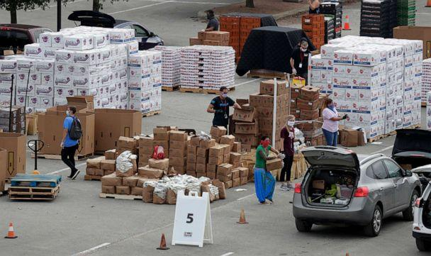 PHOTO: Workers and volunteers help load cars with food at a San Antonio Food Bank drive-through distribution during the coronavirus pandemic in San Antonio, April 7, 2020. (Eric Gay/AP, FILE)