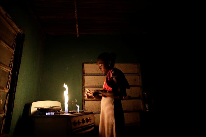 """Aidalis Guanipa, 25, a kidney disease patient, prepares her breakfast, before a day of dialysis, at her home, during a blackout in La Concepcion, Venezuela. """"I should have been born rich to be able to buy myself a new kidney,"""" said Guanipa. They get by on her 83-year-old grandmother's pension and from sales of homemade sweets. """"I have not had dialysis for two days because there has been no electricity. I am scared."""" (Photo: Ueslei Marcelino/Reuters)"""