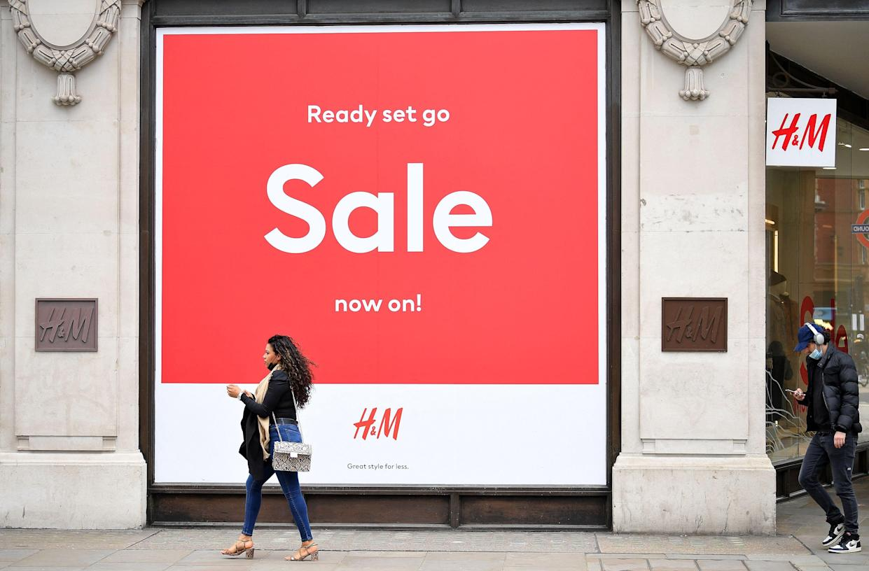 Pedestrians wearing face coverings due to Covid-19, walk past a 'Sale' sign in the window of a closed H&M clothes store on a quiet Oxford Street in central London on March 24, 2021. - Britain's annual inflation rate unexpectedly fell in February as coronavirus curbs sparked heavy discounting for clothing and footwear, official data showed Wednesday, soothing market concerns over inflationary pressures. (Photo by JUSTIN TALLIS / AFP) (Photo by JUSTIN TALLIS/AFP via Getty Images)