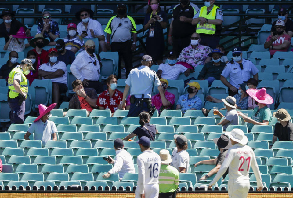 Police talk to spectators as the game is stopped after a complaint by Indian players during play on day four of the third cricket test between India and Australia at the Sydney Cricket Ground, Sydney, Australia, Sunday, Jan. 10, 2021. (AP Photo/Rick Rycroft)