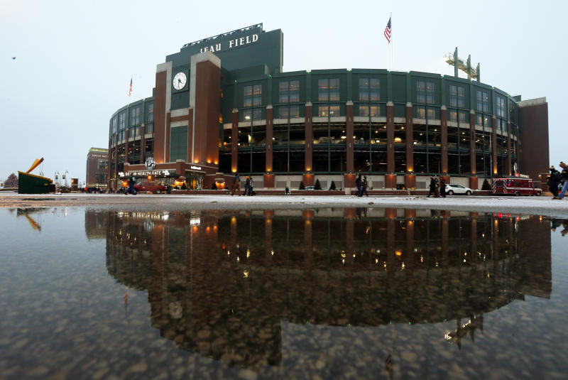 Lambeau Field is seen reflected in a puddle of water before an NFL football game between the Green Bay Packers and the Atlanta Falcons Monday, Dec. 8, 2014, in Green Bay, Wis. (AP Photo/Mike Roemer)